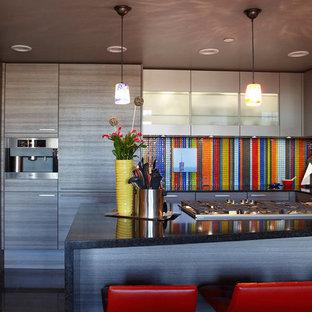 ヒューストンの小さいエクレクティックスタイルのおしゃれなキッチン (シングルシンク、フラットパネル扉のキャビネット、グレーのキャビネット、クオーツストーンカウンター、マルチカラーのキッチンパネル、ボーダータイルのキッチンパネル、パネルと同色の調理設備、磁器タイルの床、アイランドなし) の写真