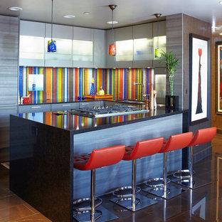 ヒューストンの小さいエクレクティックスタイルのおしゃれなキッチン (シングルシンク、フラットパネル扉のキャビネット、グレーのキャビネット、クオーツストーンカウンター、マルチカラーのキッチンパネル、ボーダータイルのキッチンパネル、パネルと同色の調理設備、磁器タイルの床、アイランドなし、茶色い床) の写真