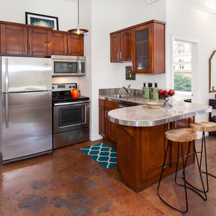 Small kitchen ideas - Example of a small u-shaped kitchen design in Los Angeles with dark wood cabinets, stainless steel appliances and a peninsula