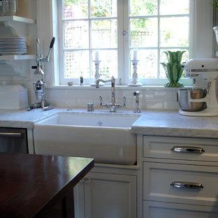 Inspiration för små klassiska vitt kök, med en rustik diskho, luckor med profilerade fronter, vita skåp, marmorbänkskiva, vitt stänkskydd, stänkskydd i tunnelbanekakel, rostfria vitvaror, mörkt trägolv, en köksö och brunt golv