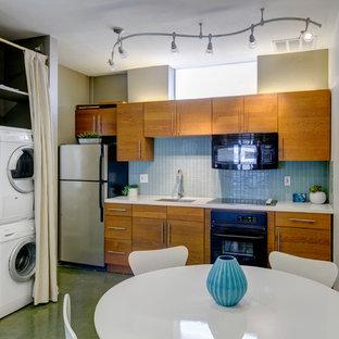 サンディエゴのコンテンポラリースタイルのおしゃれなキッチン (フラットパネル扉のキャビネット、中間色木目調キャビネット、青いキッチンパネル、黒い調理設備) の写真