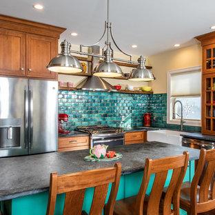 Idéer för ett klassiskt svart l-kök, med en rustik diskho, skåp i mellenmörkt trä, grönt stänkskydd, rostfria vitvaror, en köksö och bänkskiva i täljsten