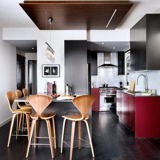 Foto de cocina en U, moderna, con armarios con paneles lisos, puertas de armario rojas, salpicadero con mosaicos de azulejos y electrodomésticos de acero inoxidable