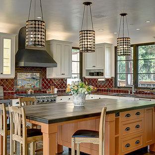サンタバーバラの中サイズの地中海スタイルのおしゃれなキッチン (アンダーカウンターシンク、落し込みパネル扉のキャビネット、白いキャビネット、タイルカウンター、赤いキッチンパネル、セラミックタイルのキッチンパネル、シルバーの調理設備の、セラミックタイルの床) の写真