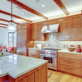 サンタバーバラの中サイズの地中海スタイルのおしゃれなキッチン (ダブルシンク、落し込みパネル扉のキャビネット、淡色木目調キャビネット、タイルカウンター、白いキッチンパネル、セラミックタイルのキッチンパネル、シルバーの調理設備の、淡色無垢フローリング) の写真