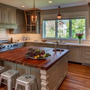 Cette photo montre une cuisine victorienne en U avec un évier encastré, un placard avec porte à panneau encastré, des portes de placard grises, une crédence blanche, une crédence en mosaïque, un électroménager encastrable, un sol en bois foncé et un îlot central.