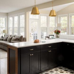 ワシントンD.C.の広いおしゃれなキッチン (ドロップインシンク、シェーカースタイル扉のキャビネット、黒いキャビネット、クオーツストーンカウンター、白いキッチンパネル、磁器タイルのキッチンパネル、黒い調理設備、磁器タイルの床、マルチカラーの床、白いキッチンカウンター) の写真