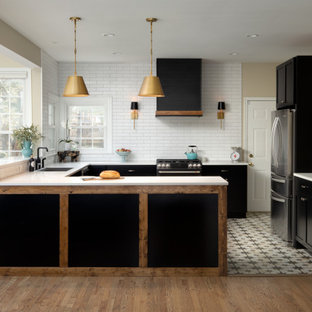 Inspiration for a large country u-shaped open plan kitchen in DC Metro with a drop-in sink, shaker cabinets, black cabinets, quartz benchtops, white splashback, porcelain splashback, black appliances, porcelain floors, a peninsula, multi-coloured floor and white benchtop.