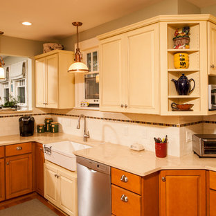 Inspiration for a country l-shaped eat-in kitchen in Detroit with white splashback, subway tile splashback, stainless steel appliances, a farmhouse sink, raised-panel cabinets, yellow cabinets, limestone benchtops, medium hardwood floors and a peninsula.