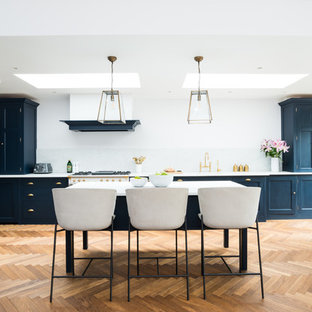 Photo of an expansive traditional galley kitchen/diner in London with a built-in sink, blue cabinets, marble worktops, white splashback, marble splashback, white appliances, white worktops, shaker cabinets, medium hardwood flooring, an island and beige floors.