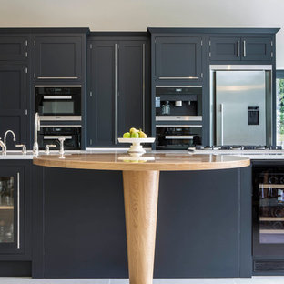 Design ideas for a traditional kitchen in Buckinghamshire with shaker cabinets, black cabinets, black appliances and an island.