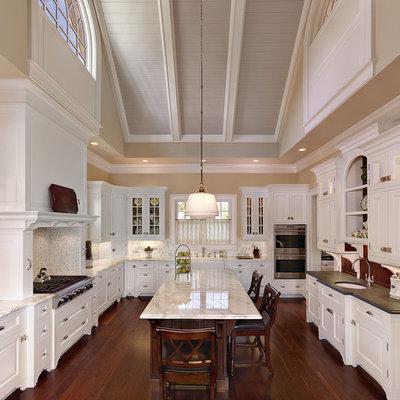 Elegant u-shaped kitchen photo in Charleston with raised-panel cabinets, white cabinets, white backsplash and an undermount sink