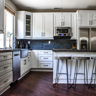Mid-sized contemporary eat-in kitchen designs - Eat-in kitchen - mid-sized contemporary l-shaped dark wood floor eat-in kitchen idea in Los Angeles with a farmhouse sink, recessed-panel cabinets, white cabinets, quartz countertops, black backsplash, stone tile backsplash, stainless steel appliances and an island