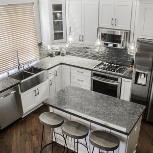 Mid-sized contemporary eat-in kitchen ideas - Mid-sized trendy l-shaped dark wood floor eat-in kitchen photo in Los Angeles with a farmhouse sink, recessed-panel cabinets, white cabinets, quartz countertops, black backsplash, stone tile backsplash, stainless steel appliances and an island