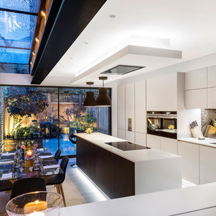 Design ideas for a contemporary galley kitchen/diner in London with a submerged sink, flat-panel cabinets, white cabinets, mirror splashback, concrete flooring, an island, grey floors and white worktops.
