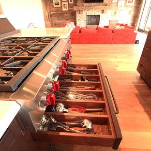 他の地域の大きいカントリー風おしゃれなキッチン (エプロンフロントシンク、落し込みパネル扉のキャビネット、濃色木目調キャビネット、クオーツストーンカウンター、マルチカラーのキッチンパネル、石スラブのキッチンパネル、パネルと同色の調理設備、無垢フローリング、茶色い床、白いキッチンカウンター) の写真
