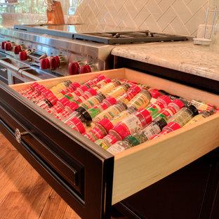Große Klassische Wohnküche in L-Form mit Landhausspüle, profilierten Schrankfronten, schwarzen Schränken, Granit-Arbeitsplatte, Küchenrückwand in Grau, Rückwand aus Glasfliesen, Küchengeräten aus Edelstahl, braunem Holzboden und Kücheninsel in Milwaukee