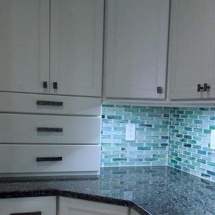 Inspiration för ett mellanstort maritimt kök, med en undermonterad diskho, luckor med infälld panel, vita skåp, bänkskiva i återvunnet glas, grönt stänkskydd, stänkskydd i glaskakel, rostfria vitvaror, klinkergolv i keramik och en köksö