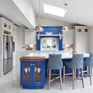 Idee per un'ampia cucina tradizionale con lavello integrato, ante a persiana, ante blu, top in quarzite, paraspruzzi bianco, paraspruzzi in lastra di pietra, elettrodomestici in acciaio inossidabile, pavimento con piastrelle in ceramica e isola