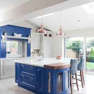 Expansive transitional l-shaped open plan kitchen in Dublin with an integrated sink, louvered cabinets, blue cabinets, quartzite benchtops, white splashback, stone slab splashback, stainless steel appliances, ceramic floors and with island.