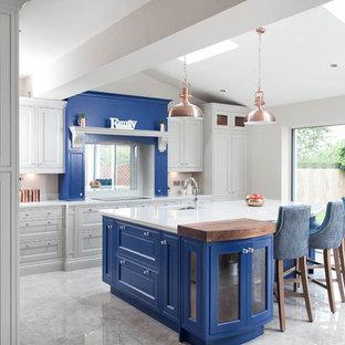 Foto di un'ampia cucina classica con lavello integrato, ante a persiana, ante blu, top in quarzite, paraspruzzi bianco, paraspruzzi in lastra di pietra, elettrodomestici in acciaio inossidabile, pavimento con piastrelle in ceramica e isola