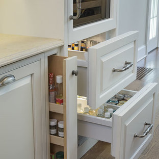 Expansive traditional galley kitchen/diner in Boston with raised-panel cabinets, white cabinets, medium hardwood flooring, multi-coloured splashback, an island, limestone worktops, brown floors, integrated appliances and beige worktops.