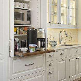 ボストンの巨大なトラディショナルスタイルのおしゃれなキッチン (レイズドパネル扉のキャビネット、白いキャビネット、マルチカラーのキッチンパネル、シルバーの調理設備、無垢フローリング、ライムストーンカウンター、磁器タイルのキッチンパネル、茶色い床、ベージュのキッチンカウンター) の写真