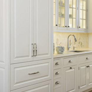 Idéer för att renovera ett mycket stort vintage beige beige kök, med luckor med upphöjd panel, vita skåp, flerfärgad stänkskydd, mellanmörkt trägolv, en köksö, en undermonterad diskho, bänkskiva i kalksten, stänkskydd i porslinskakel, brunt golv och integrerade vitvaror