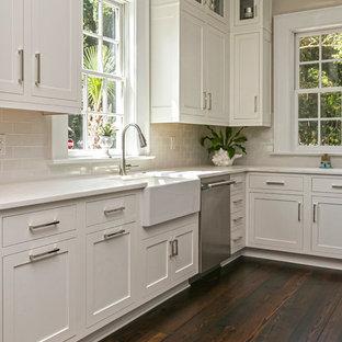 Inspiration pour une cuisine traditionnelle avec un évier de ferme, un placard à porte shaker, des portes de placard blanches, une crédence grise, une crédence en carrelage métro et un sol en bois foncé.