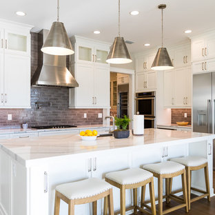 Large farmhouse kitchen pictures - Inspiration for a large cottage medium tone wood floor and brown floor kitchen remodel in Jacksonville with an undermount sink, shaker cabinets, white cabinets, quartz countertops, gray backsplash, porcelain backsplash, stainless steel appliances, an island and multicolored countertops