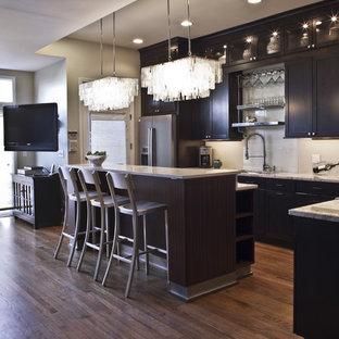 Inspiration for a contemporary l-shaped kitchen remodel in Chicago with an undermount sink, recessed-panel cabinets, dark wood cabinets, marble countertops, white backsplash, glass tile backsplash, stainless steel appliances and an island