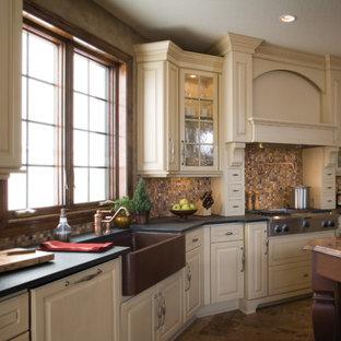 Diseño de cocina clásica con fregadero sobremueble, armarios con paneles con relieve, puertas de armario blancas, salpicadero metalizado, salpicadero de azulejos de vidrio, electrodomésticos con paneles, suelo de baldosas de porcelana y una isla