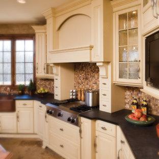 Imagen de cocina en L, clásica, con fregadero sobremueble, armarios con paneles con relieve, puertas de armario blancas, salpicadero metalizado, salpicadero de metal, electrodomésticos de acero inoxidable, suelo de baldosas de porcelana y una isla