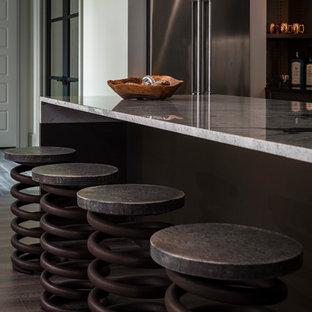 Foto di una cucina industriale di medie dimensioni con lavello sottopiano, ante lisce, ante marroni, top in granito, paraspruzzi beige, elettrodomestici in acciaio inossidabile, parquet scuro, isola e pavimento marrone