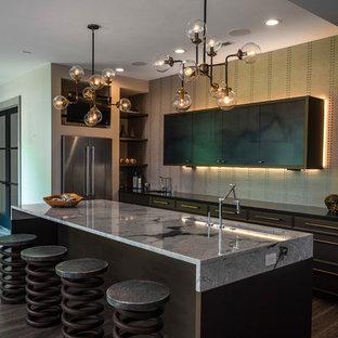 インディアナポリスの中サイズのインダストリアルスタイルのおしゃれなキッチン (アンダーカウンターシンク、フラットパネル扉のキャビネット、茶色いキャビネット、御影石カウンター、ベージュキッチンパネル、シルバーの調理設備の、濃色無垢フローリング、茶色い床) の写真