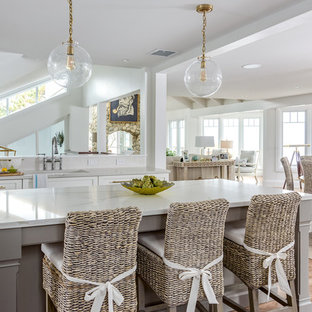Open concept kitchen - beach style light wood floor open concept kitchen idea in Boston with an undermount sink, shaker cabinets, white cabinets, an island and white countertops