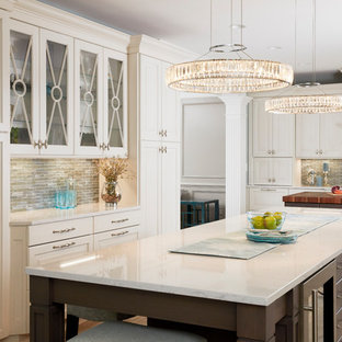 Expansive traditional u-shaped open plan kitchen in Baltimore with a farmhouse sink, raised-panel cabinets, white cabinets, quartz benchtops, blue splashback, mosaic tile splashback, stainless steel appliances, porcelain floors, multiple islands, grey floor and white benchtop.