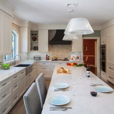 Enclosed kitchen - traditional l-shaped enclosed kitchen idea in Philadelphia with stone tile backsplash, recessed-panel cabinets, paneled appliances and a farmhouse sink