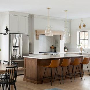 Klassische Küche in L-Form mit Unterbauwaschbecken, Schrankfronten im Shaker-Stil, weißen Schränken, Küchenrückwand in Weiß, Rückwand aus Stein, Küchengeräten aus Edelstahl, hellem Holzboden, Kücheninsel, beigem Boden und weißer Arbeitsplatte in Minneapolis