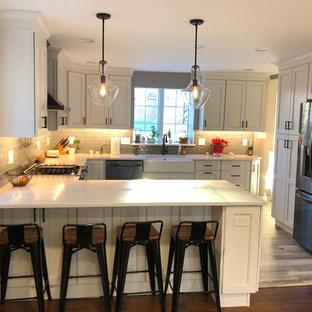 Large transitional u-shaped eat-in kitchen in Philadelphia with a farmhouse sink, recessed-panel cabinets, beige cabinets, quartz benchtops, grey splashback, porcelain splashback, black appliances, vinyl floors, a peninsula, multi-coloured floor and white benchtop.