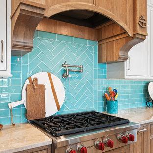 他の地域の広いトロピカルスタイルのおしゃれなキッチン (アンダーカウンターシンク、インセット扉のキャビネット、白いキャビネット、珪岩カウンター、青いキッチンパネル、ガラスタイルのキッチンパネル、シルバーの調理設備、淡色無垢フローリング、茶色い床、ベージュのキッチンカウンター、板張り天井) の写真