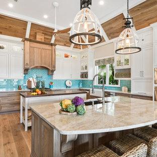 Idéer för att renovera ett stort tropiskt beige beige kök, med en undermonterad diskho, luckor med profilerade fronter, vita skåp, bänkskiva i kvartsit, blått stänkskydd, stänkskydd i glaskakel, rostfria vitvaror, ljust trägolv, flera köksöar och brunt golv