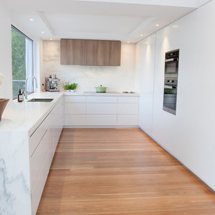 Photo of a contemporary u-shaped separate kitchen in Melbourne with an undermount sink, flat-panel cabinets, white cabinets, grey splashback, panelled appliances, medium hardwood floors, no island, brown floor and grey benchtop.