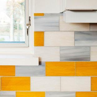 Mid-Century Wohnküche in L-Form mit Waschbecken, flächenbündigen Schrankfronten, hellen Holzschränken, Quarzit-Arbeitsplatte, Küchenrückwand in Gelb, Rückwand aus Glasfliesen und Küchengeräten aus Edelstahl in Atlanta