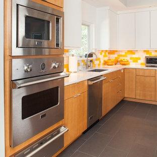Mid-Century Wohnküche in L-Form mit Waschbecken, flächenbündigen Schrankfronten, hellen Holzschränken, Quarzit-Arbeitsplatte, Küchenrückwand in Gelb, Rückwand aus Glasfliesen, Küchengeräten aus Edelstahl und grauem Boden in Atlanta