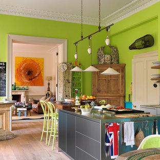 ロンドンのエクレクティックスタイルのおしゃれなアイランドキッチン (一体型シンク、フラットパネル扉のキャビネット、グレーのキャビネット、ステンレスカウンター、淡色無垢フローリング) の写真