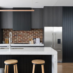 Inspiration for a contemporary galley eat-in kitchen in Sydney with an undermount sink, flat-panel cabinets, grey cabinets, red splashback, brick splashback, stainless steel appliances, medium hardwood floors, with island, brown floor and white benchtop.