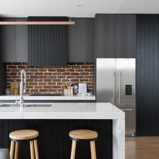 シドニーのコンテンポラリースタイルのおしゃれなキッチン (アンダーカウンターシンク、フラットパネル扉のキャビネット、グレーのキャビネット、赤いキッチンパネル、レンガのキッチンパネル、シルバーの調理設備の、無垢フローリング、茶色い床、白いキッチンカウンター) の写真