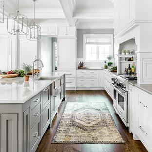 Große Klassische Küche mit Landhausspüle, Kassettenfronten, weißen Schränken, Küchenrückwand in Weiß, Rückwand aus Keramikfliesen, Küchengeräten aus Edelstahl, Kücheninsel, braunem Boden und dunklem Holzboden in Chicago