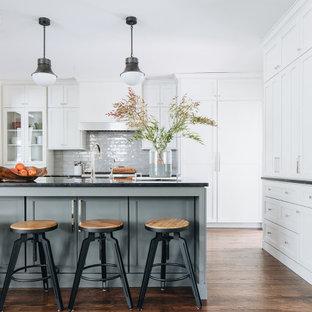 Inredning av ett klassiskt mellanstort svart svart kök, med en undermonterad diskho, skåp i shakerstil, vita skåp, marmorbänkskiva, grått stänkskydd, stänkskydd i keramik, rostfria vitvaror, mörkt trägolv, en köksö och brunt golv